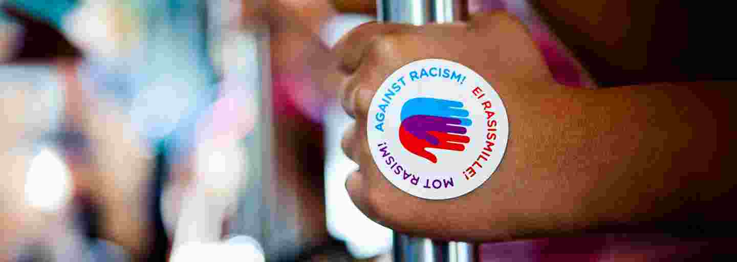 Hand with an Against Racism! logo sticker holding a bar in a tram.