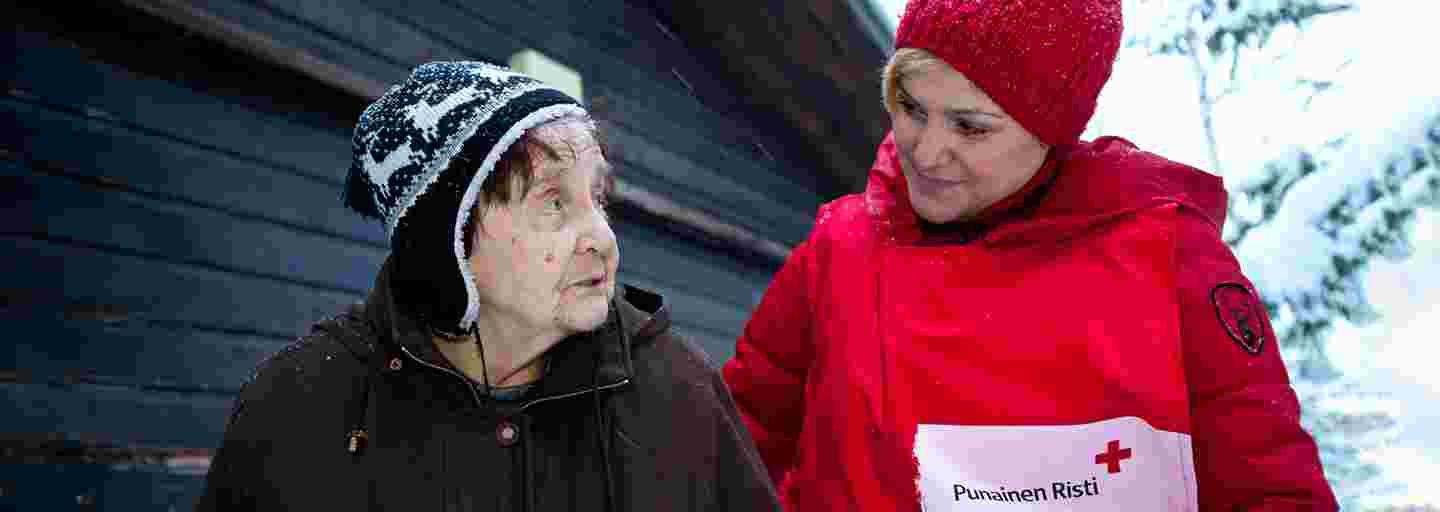 Two women standing side by side in a wintry landscape. The younger woman, wearing a Red Cross volunteer vest, is looking gently at the older woman.
