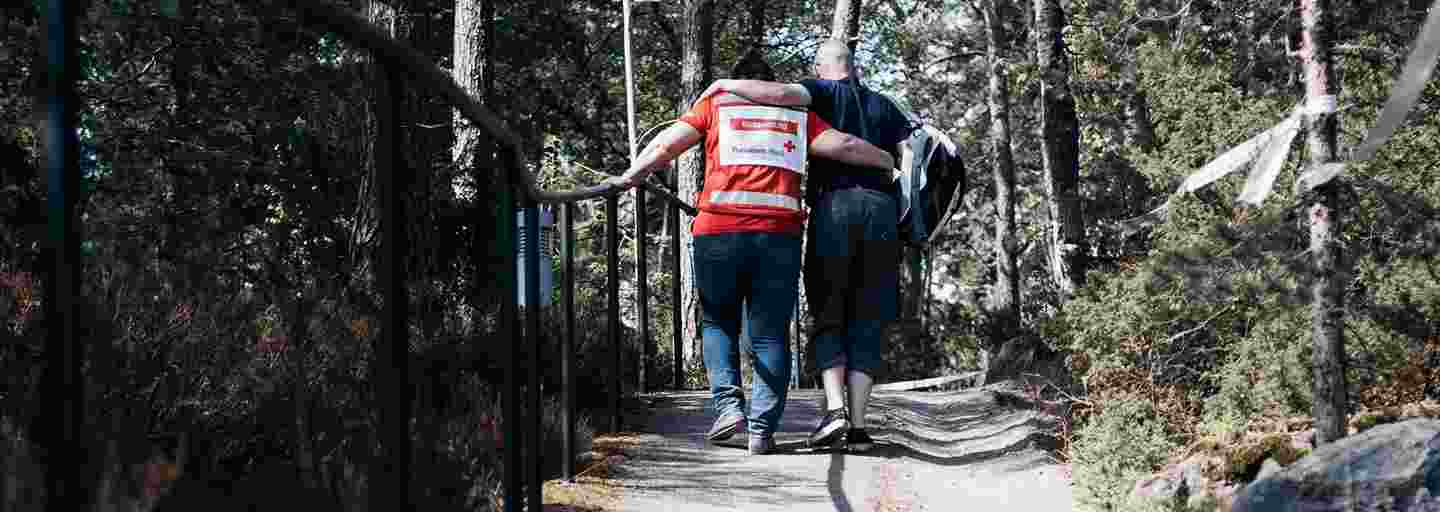 A man leaning on a Red Cross volunteer while walking uphill on a road lined by trees.