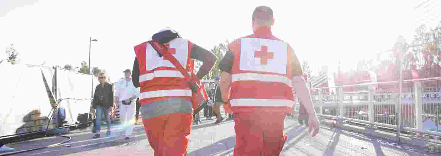 On first aid duty at an outdoor event, a man and a woman wearing Red Cross uniforms walk towards the sunset.